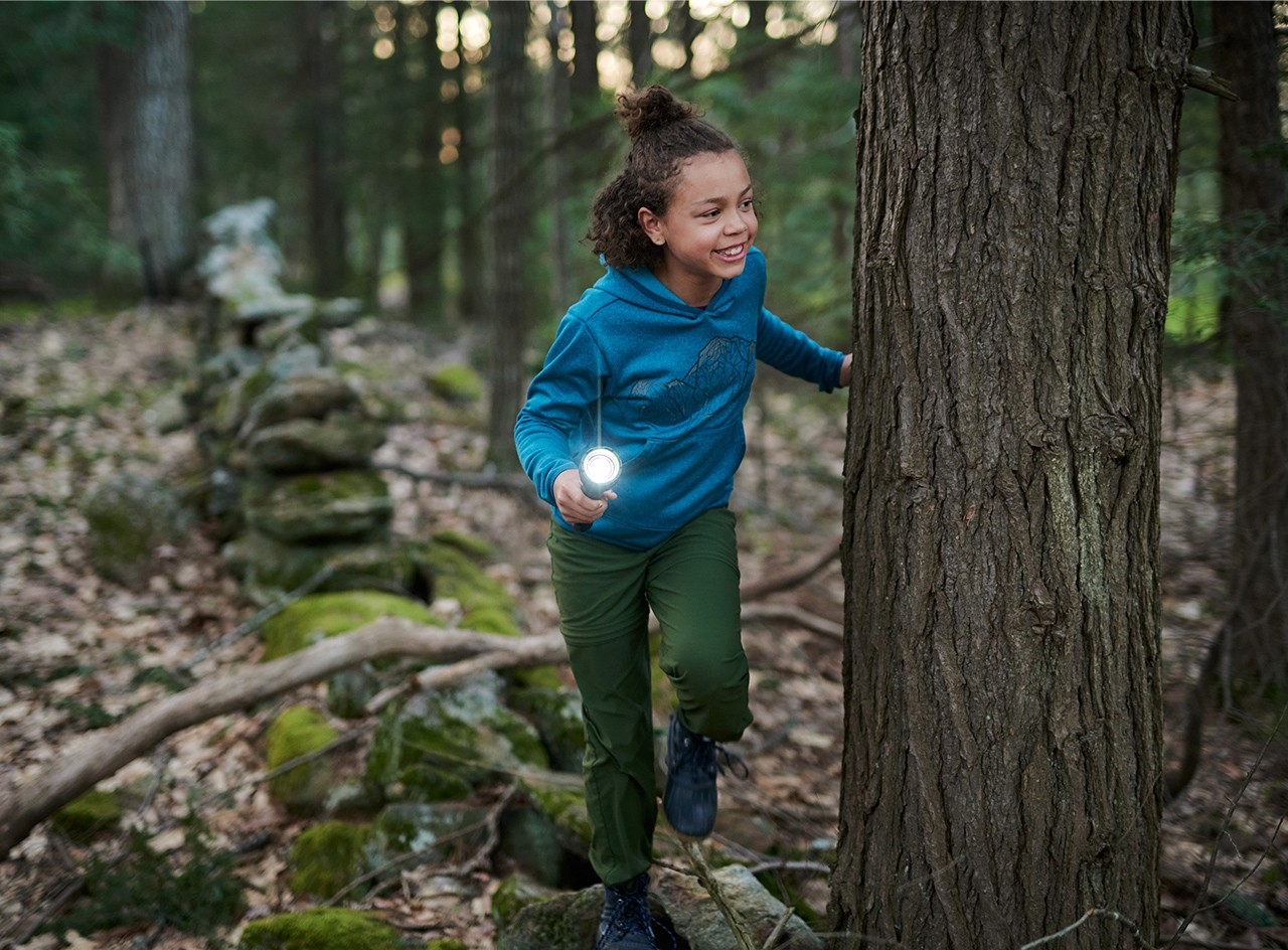 A young girl in an L.L. Bean sweatshirt with a flashlight playing flashlight tag