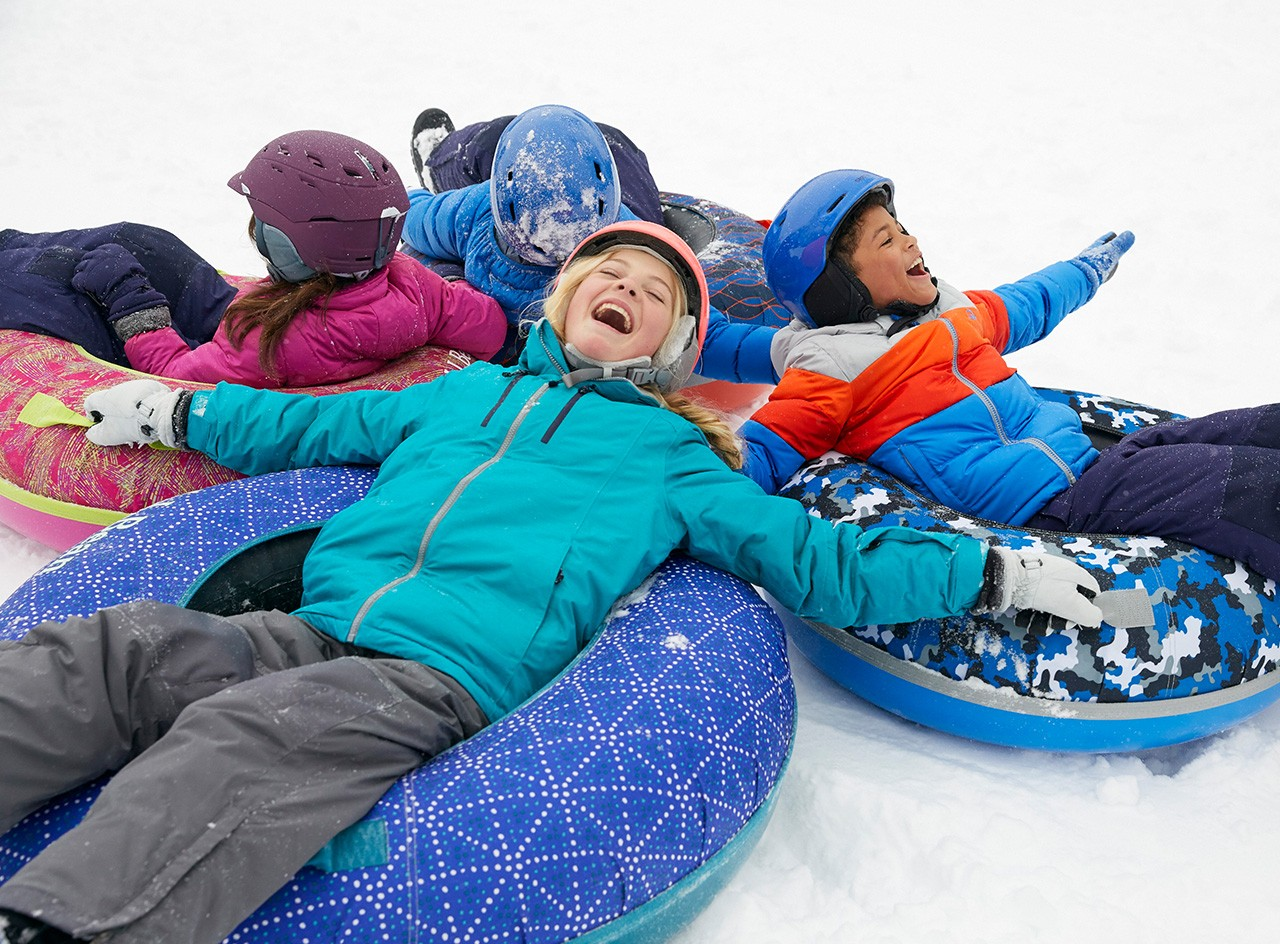 Laughing children sliding on L.L. Bean Sonic Snowtubes.