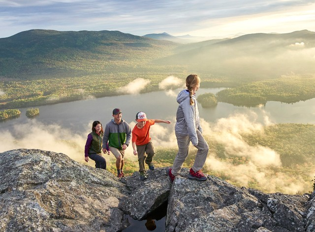 Family of 4 enjoying sunrise view on a mountaintop.