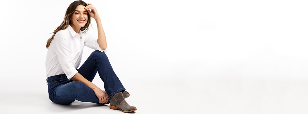 Woman lounging in True Shape stretch jeans.