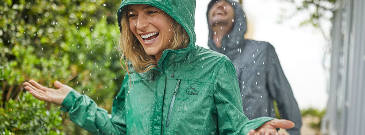 Woman outside in rainwear. Man in rainwear in the backgound.