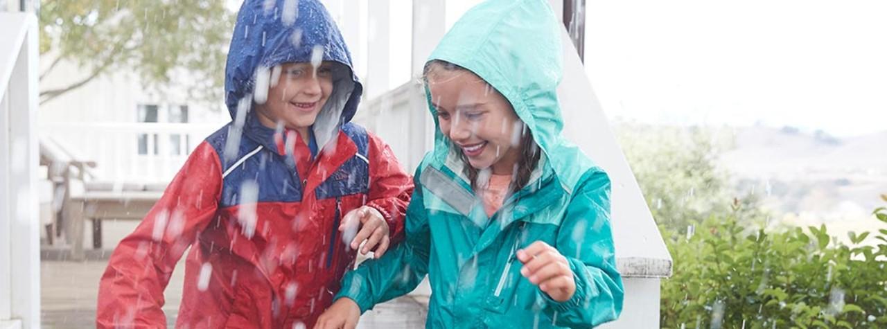 Kids outside in the rain wearing rain gear.