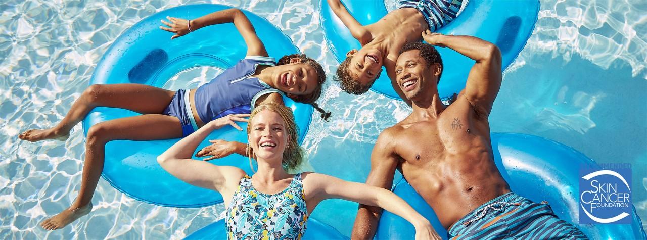Family of 4 floating in a pool wearing L. L. Bean swimwear.