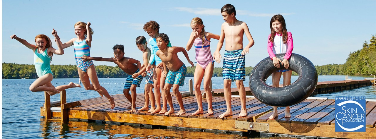 9 happy kids wearing L. L. Bean swimwear, on a dock getting ready to jump in the water.