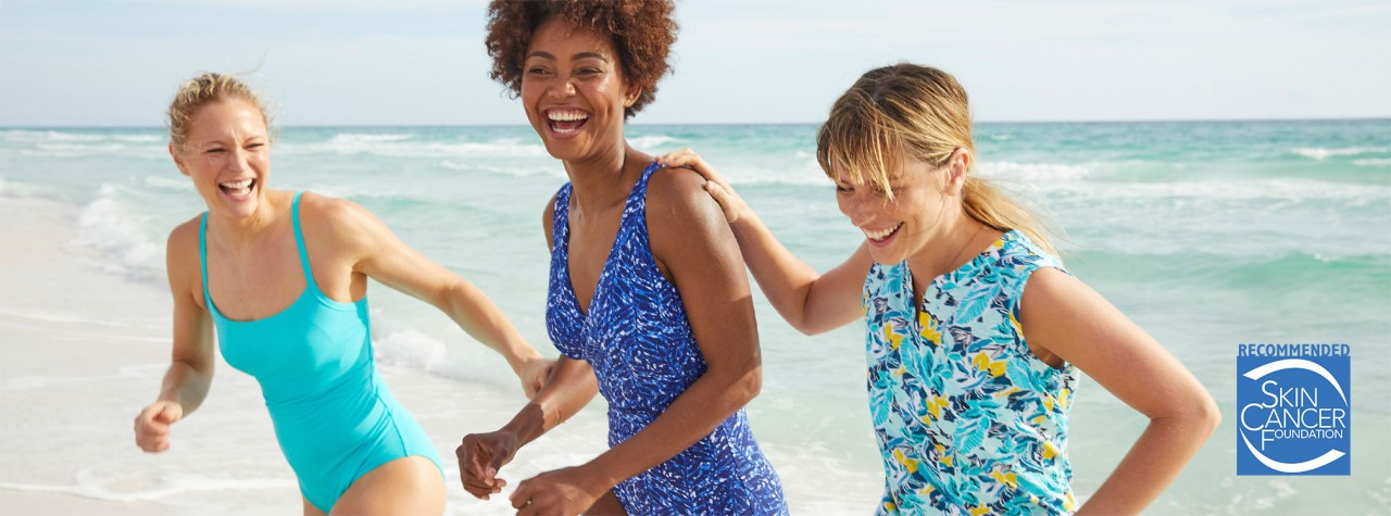 Close-up of 3 women laughing at the beach wearing L. L. Bean swimwear.