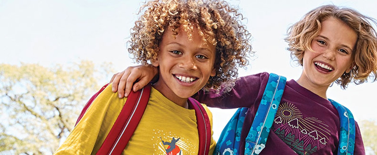 Close-up of 2 smiling kids wearing L. L. Bean backpacks and t-shirts.