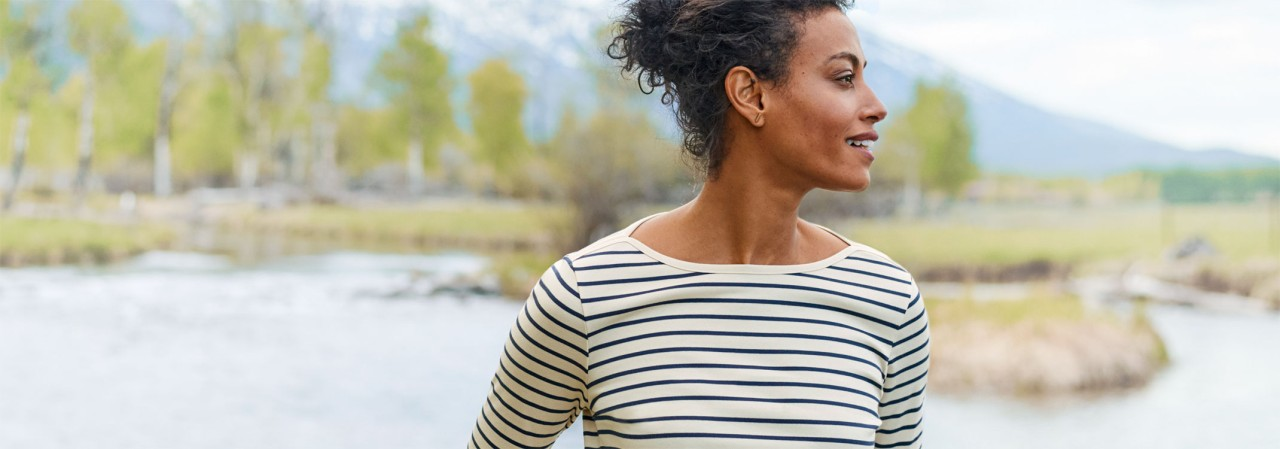 Close up of smiling woman outside wearing an L. L. Bean long-sleeve, striped pima cotton tee.