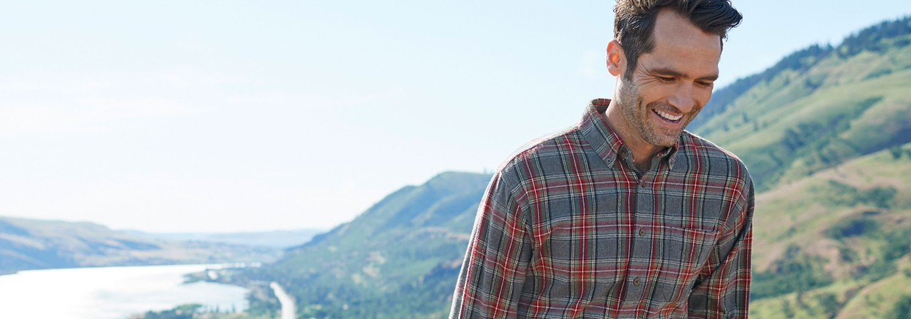 A man outside in a flannel shirt, beautiful lake and mountains in background.