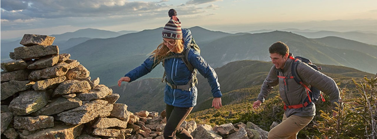 A woman and man hiking on a mountaintop, appropriately dressed for cool weather, with beautiful mountain views behind them.