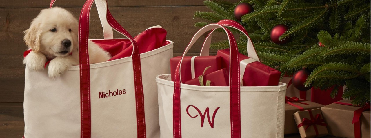 2 red monogrammed Boat & Totes by a christmas tree, a puppy peeking out of one tote.