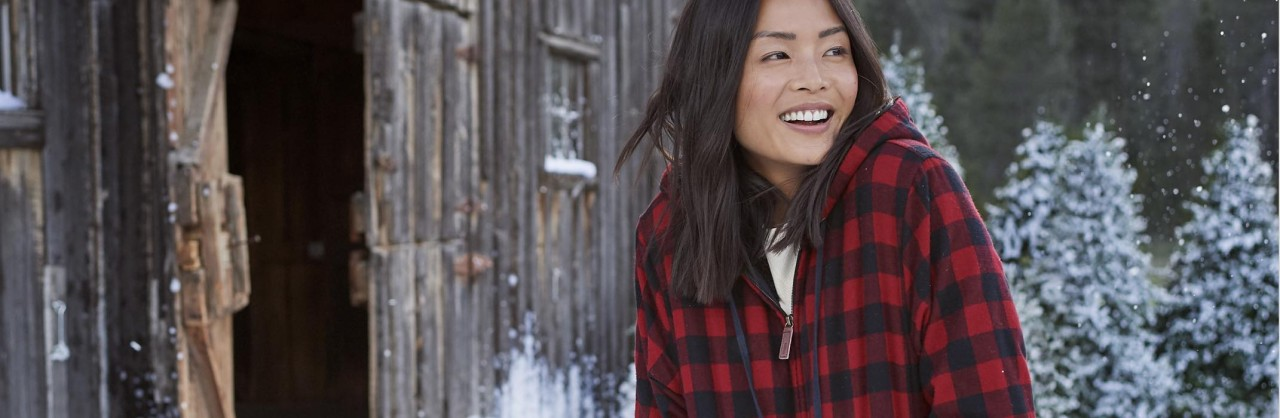 Woman outside in the snow wearing a hooded flannel shirt.