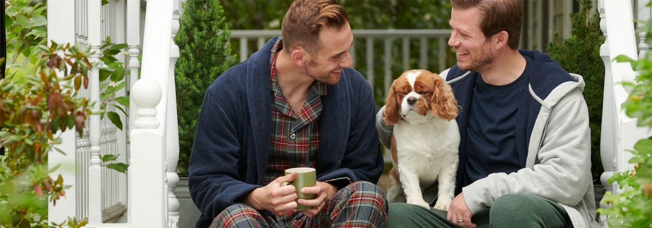 Two men and a dog, sitting on a porch in their pajamas.