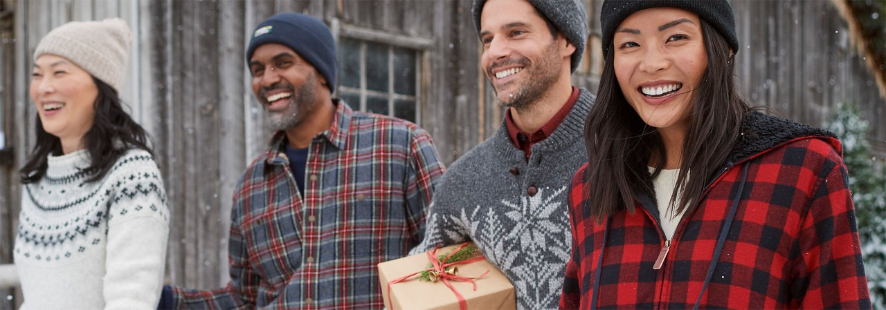 Happy people carrying holiday gifts outside in winter, some wearing flannel shirts.