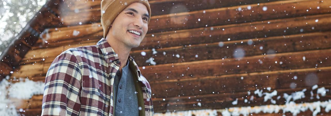 Man outside in winter wearing flannel shirt.