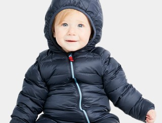 Close-up of smiling toddler in a hooded down jacket.