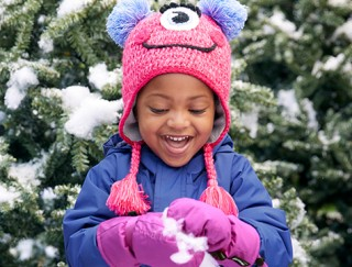 Close-up of happy toddler playing in the snow in L. L. Bean outerwear