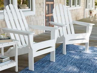 White adirondack chairs on a porch.