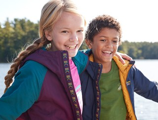 Close-up of happy boy and girl outside, arms over shoulders, wearing L.L.Bean apparel and outerwear.