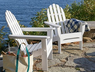 White adirondack chairs on a patio overlooking the water