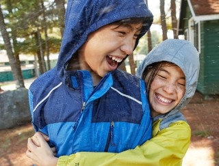 Close-up of happy boy and girl hugging outside, wearing L.L.Bean apparel and outerwear.