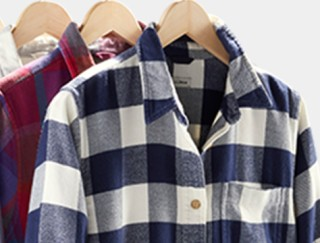 Close-up of 3 hanging flannel shirts.