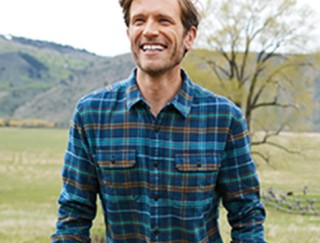 Smiling man outside in a flannel shirt.