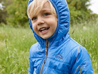 Happy toddler outside wearing lightweight down jacket with hood up.