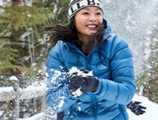 Close-up of woman outside in winter, getting ready to throw a snowball.