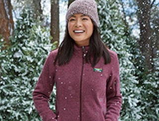 Smiling woman outside in winter wearing a fleece jacket and hat.