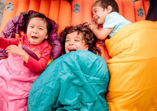Kids in sleeping bags having fun