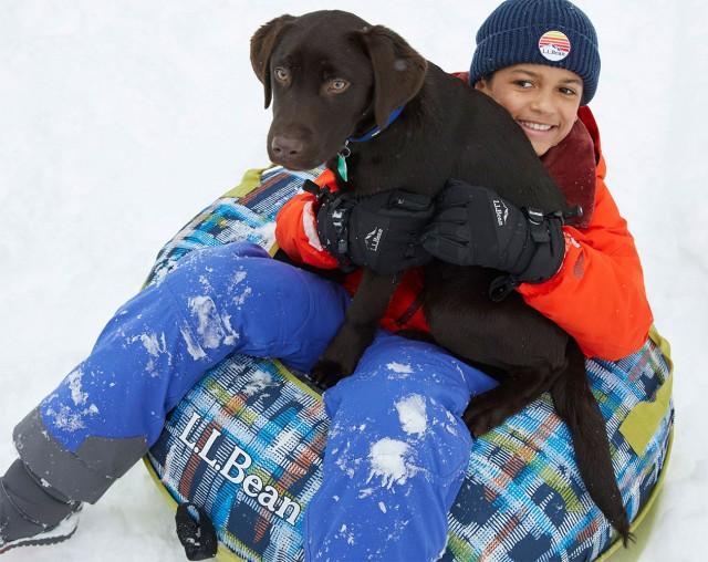 Boy on snowtube with dog