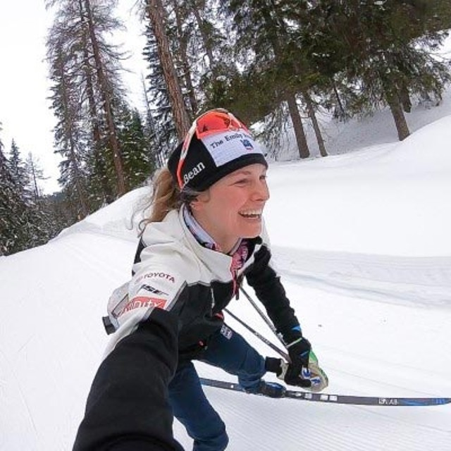 Jessie Diggins smiling and skiing.