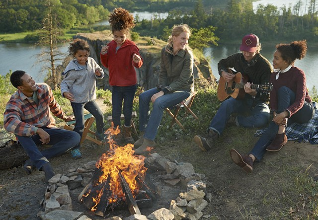 Several people outside sitting around a campfire, one playing guitar, kids dancing.