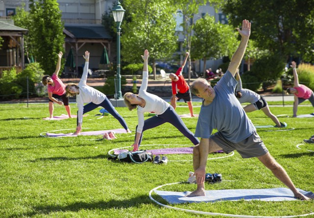 Yoga class in progress outside on the grass.