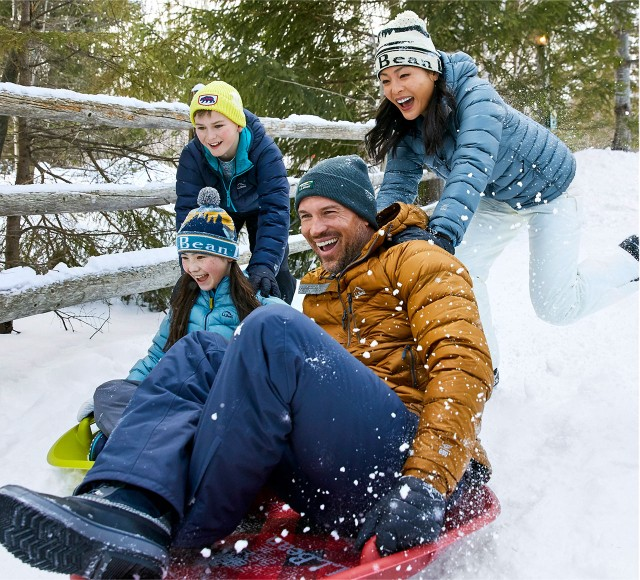 Family of 4 sledding and laughing outside in the snow.