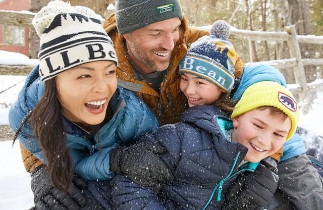 Family of four having fun outside in the snow.