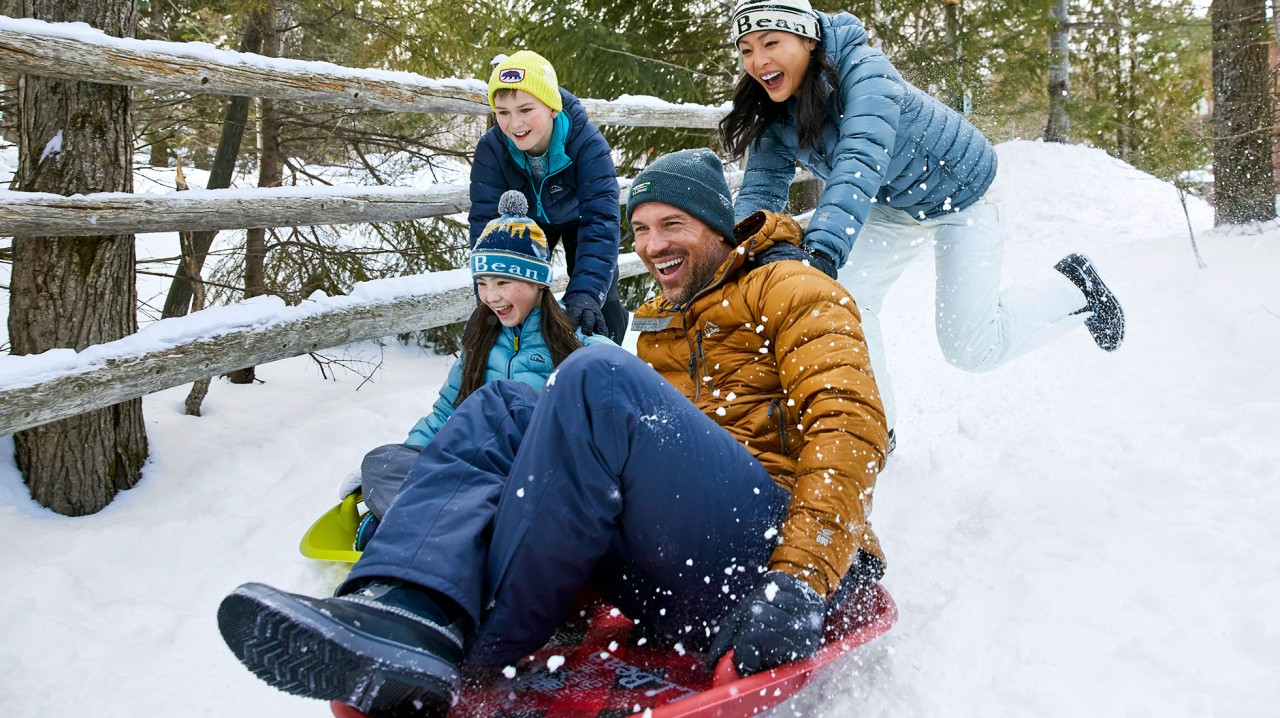 Family of four sledding.