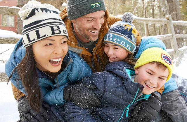 Family of four laughing and playing in the snow.