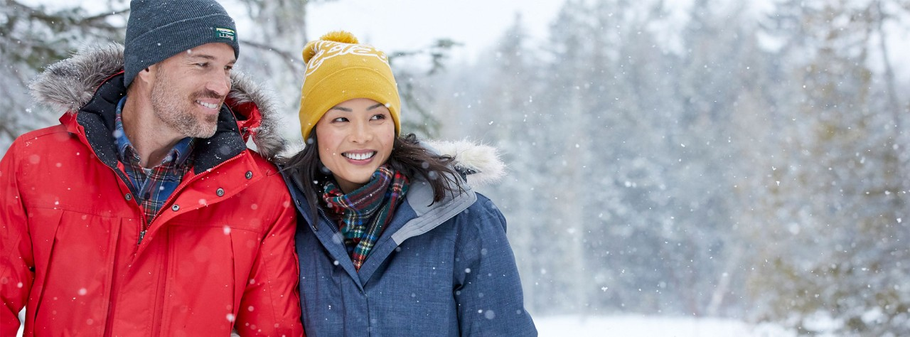 Happy couple in cozy outerwear walking on a snowy day.