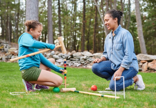 A mom and daughter setting up croquet in the backyard.
