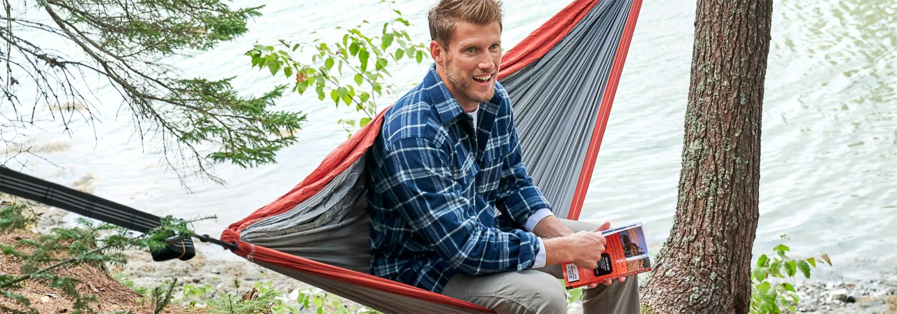 A mn outside in a hammock wearing a flannel shirt.