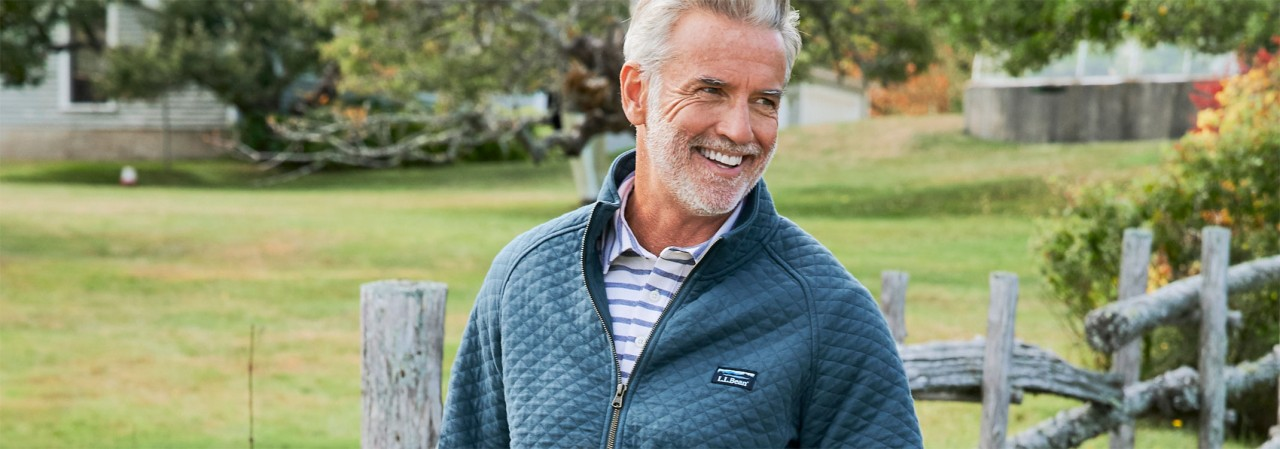 Close-up of a man outside in spring wearing a full-zip quilted sweatshirt.
