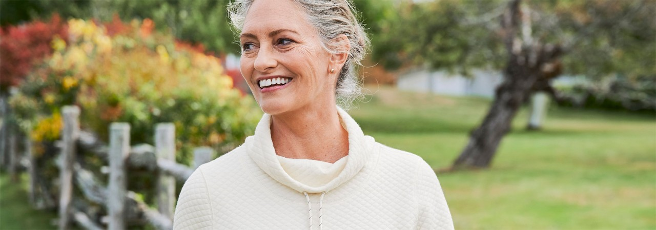 Close-up of a woman outside in spring wearing a quilted pullover.