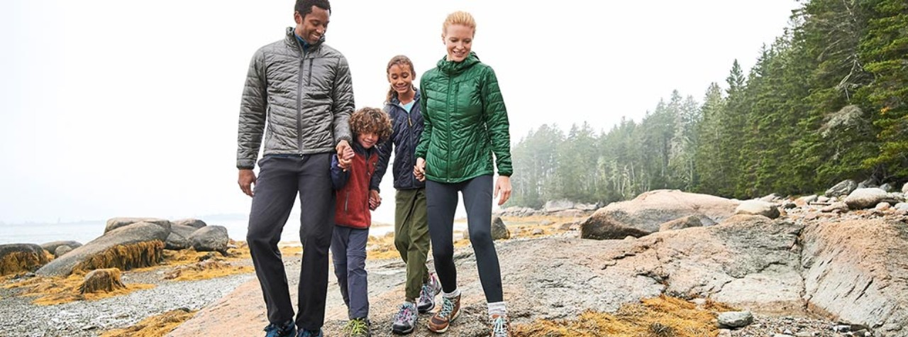 A family of 4 walking along a rocky coast on a cloudy day.