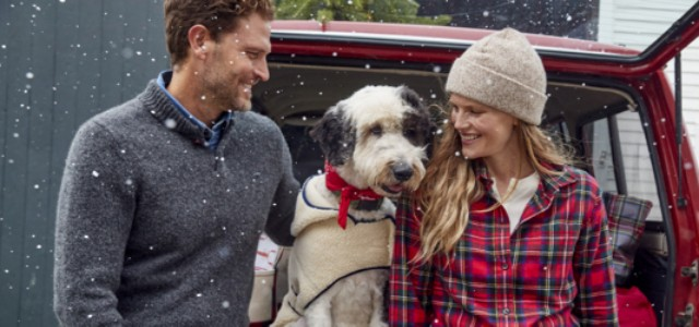 A happy couple looking at their cute dog in a fleece sweater, as he sits in the back of a car, hatch up.