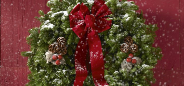 A holiday wreath with a dusting of snow on it, hanging on a red door.