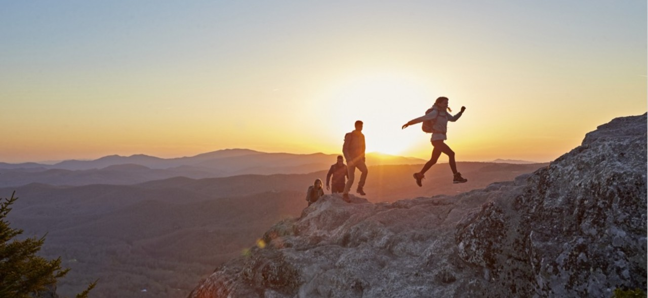 A family hiking up a mountain at sun set.