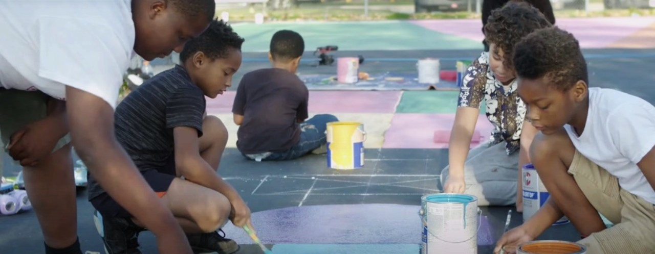 Children outdoors painting on a playground.