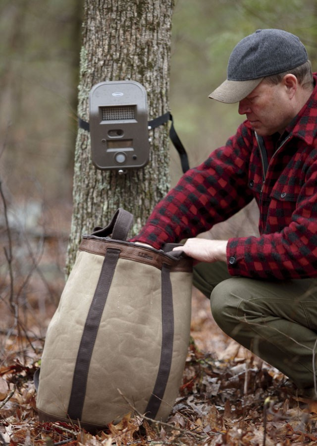 A man in red and black checked wool jacket crouching by a tree with a game camera strapped to it, reaching into his pack.