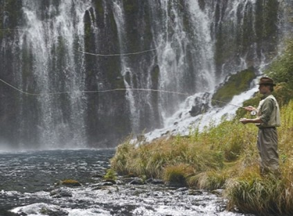 Image of a man fly fishing near a waterfall.